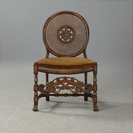 Chair, 1920s, carved decoration, perforated back, seat and back in cane, loose seat in the textile, its height about 45 cm. Price est.: SEK 2000 Stockholms Auktionsverk