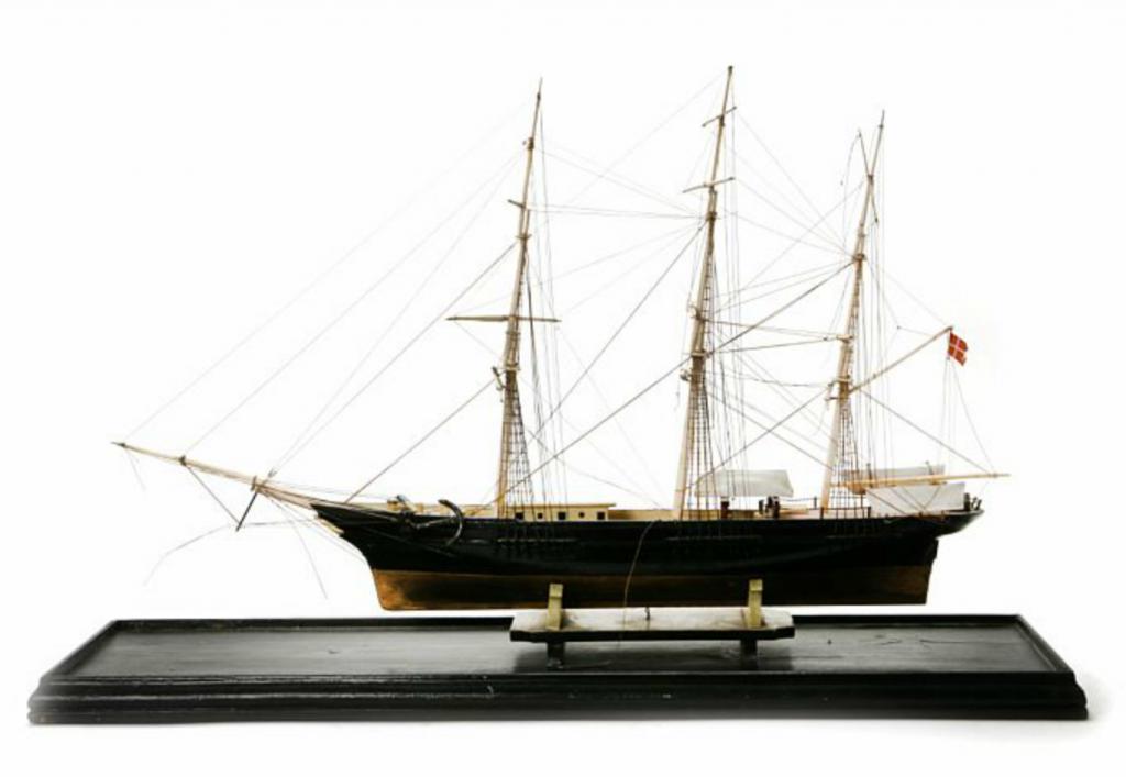 A 19th/20th century wood ship's model of a schooner H. 40 cm L. 63 cm. Showcase H. 44 cm. L. 70 cm. B. 26 cm. Provenance: Shipowner Nyholm, Elsinore Price est.: € 540