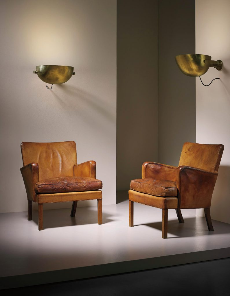 KAARE KLINT Pair of early 'Easy' armchairs, model no. 5313 designed 1927, produced from 1936  Niger leather, Cuban mahogany. Each: 82 x 68 x 73.5 cm (32 1/4 x 26 3/4 x 28 7/8 in.) Executed by cabinetmakers Rud. Rasmussen A/S, Copenhagen, Denmark. Underside of one chair with manufacturer's paper label RUD. RASMUSSENS/SNEDKERIER/45 NØRREBROGADE/KØBENHAVN, faded handwritten inventory number and architect's monogrammed paper label. Estimate £30,000 - 40,000